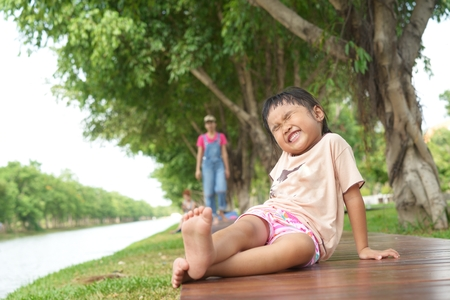 Big funny face from Thai kid in the green garden on relax pose photo