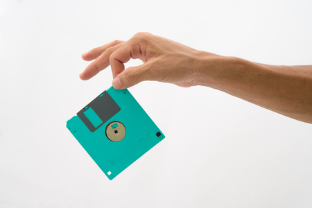 Hand hold green floppy disc on isolated white background photo