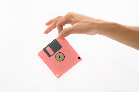 Hand hold red floppy disc on isolated white background photo