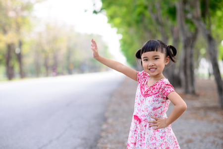 Asian kid waving call  on the side of the road