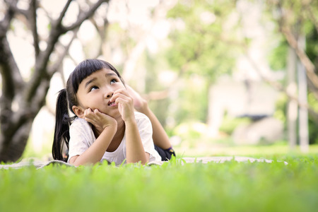 Asian kid thinking while playing in the garden