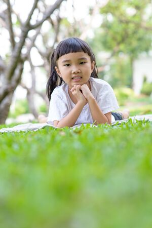 Asian kid portrait with relax pose in the green garden