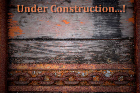 web page under construction: Old wood and rust chain background with word Under Construction Stock Photo