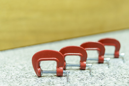 c clamp: Red C Clamp Row on the rock table with wood background Stock Photo