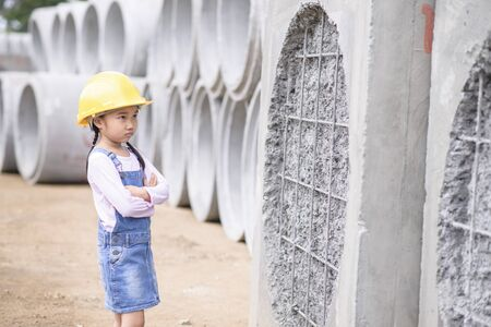 Kid civil engineer inspecting wire mesh on huge concrete pipe wall with worry mood