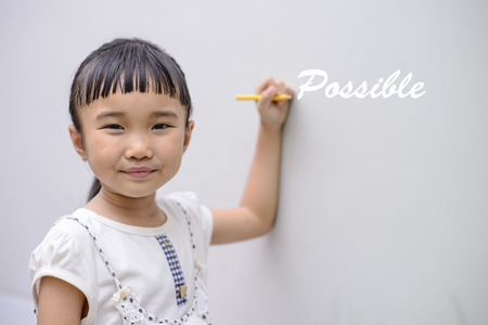 Kid write white possible word on wall with smiling face