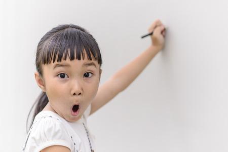 cara sorpresa: Escritura Kid en la pared con cara de sorpresa Foto de archivo