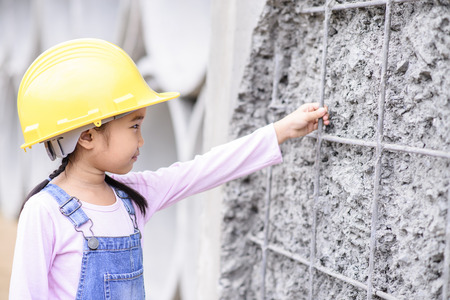 Kid civil engineer inspecting wire mesh on huge concrete pipe wall with good mood Stock Photo