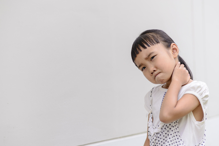 hand rubbing: Kid on neckacke pose and pain mood with grey background