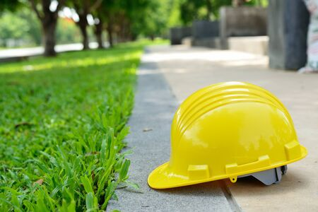 greenfield: Yellow safety helmet on concrete floor in the green garden building site