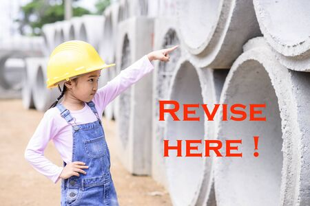 revise: Kid civil engineer inspecting the huge concrete pipe and point to revise point