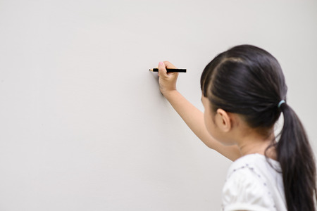 Kid write black font on wall with blur face