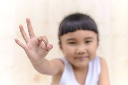 ok symbol: Kid with hand ok symbol and blur face on woodwall background