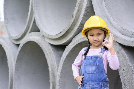 ok: Kid civil engineer inspecting  huge concrete pipe ok with that and shown symbol