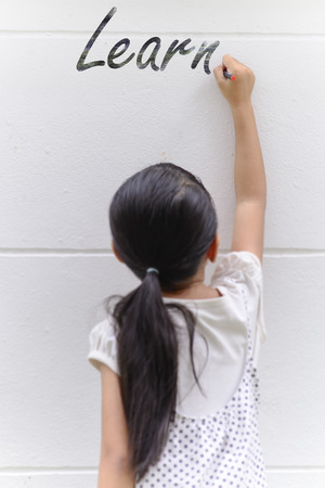 Kid writing learn word on wall with her black pencil