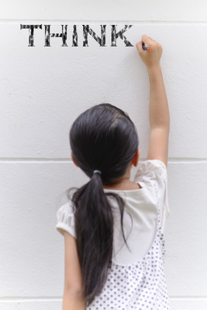 Kid writing think word on wall with her black pencil