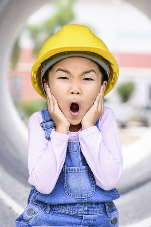 Kid with surprise pose while working in construction site Stock Photo