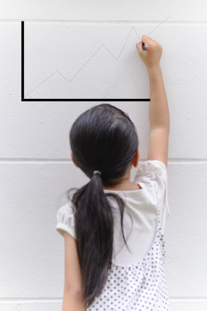 Kid writing line graph on wall with her black pencil