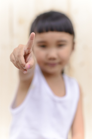 Kid hand point symbol and blur face on wood wall background Stock Photo