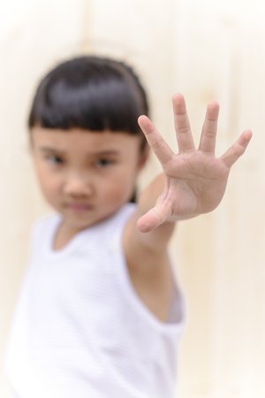 Kid make stop symbol and blur serious face on wall background