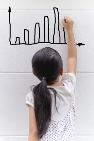 Kid writing bar graph on wall with her black pencil