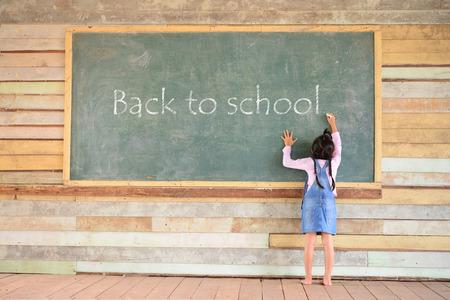 persona escribiendo: Kid escribir de nuevo a la fuente de la escuela en la vieja pizarra verde Foto de archivo