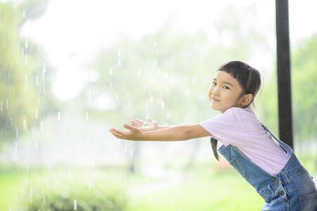 Little Asian girl enjoy playing in the rainy day; Raining in the green garden