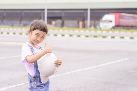 Little girl with white helmet in warehouse center background; Transportation work; Thumb up; Vintage tone