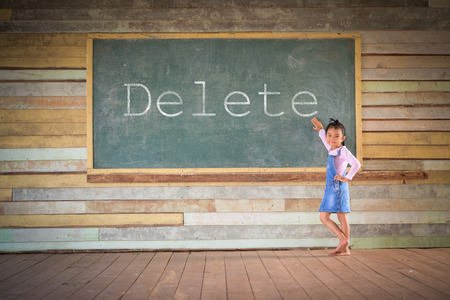 Little girl clear the green chalkboard in the old class room; Delete word on board Stock Photo