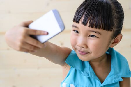 Little girl selfie by smartphone with blur wood background Stock Photo