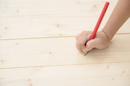 Kid hand hold red pencil and writing on wood floor