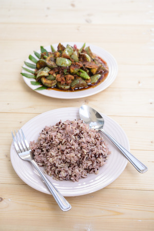 Thai food; Red rice; Pork with eggplant in Thai spicy chilli sauce; Wood background Stock Photo