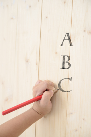 Kid hand hold red pencil and writing abc on wood wall