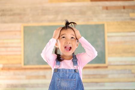 Little girl crezy pose blank green blackboard