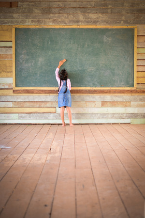 Little girl clear the old green chalkboard in the old class room Stock Photo