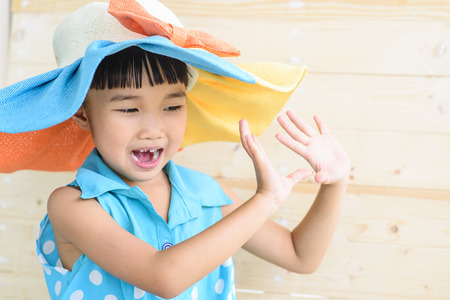 Little girl pose with the hat on her head and blur wood background