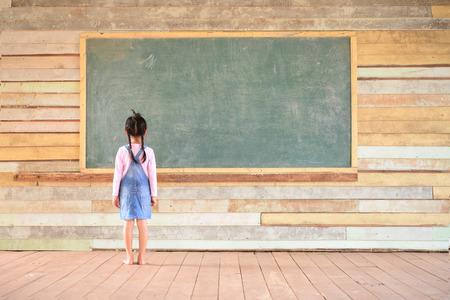 Little girl look at blank green blackboard