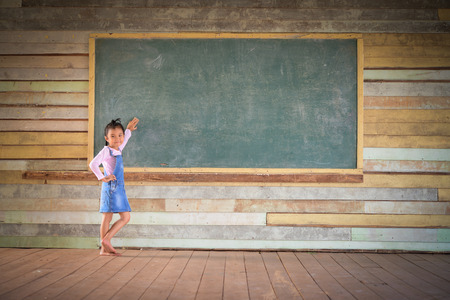 Little girl clear the green chalkboard in the old class room