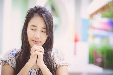 Beautiful Asian woman praying; Blur background; Vintage tone