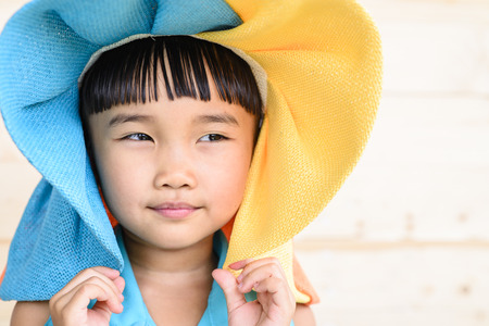 Little girl put the hat on her head with wood background