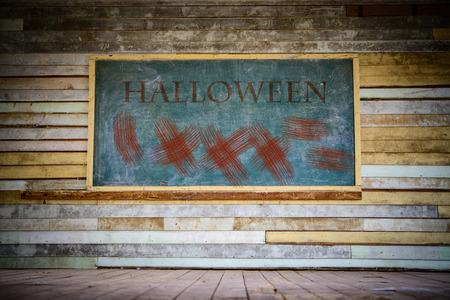 Old green chalkboard with red halloween word and wood wall Stock Photo