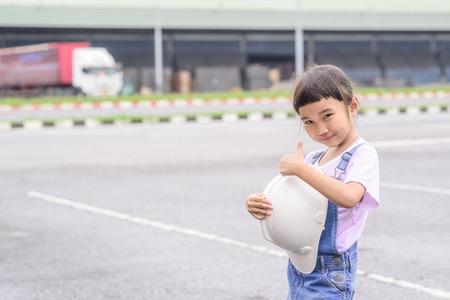 Little girl with white helmet in warehouse center background; Transportation work; Thumb up