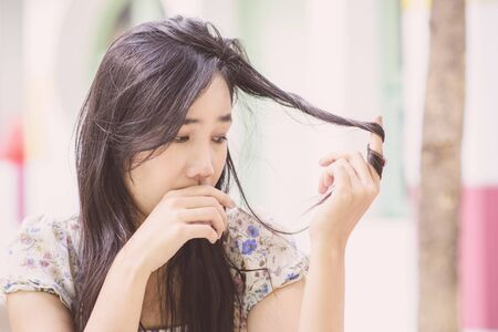 Asian woman thinking; Vintage tone; Sad mood; Hair health checking Stock Photo