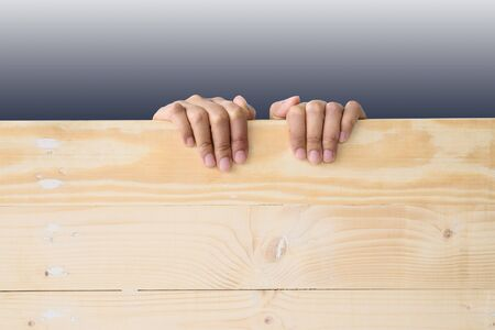 Hand holding wood with isolated dark background