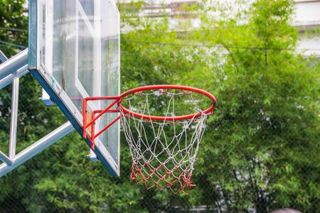 outdoor basketball court: Basketball hoop in the park with green trees as background.