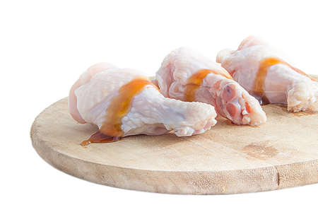 cutting boards: raw chicken legs on wooden cutting boards on white background