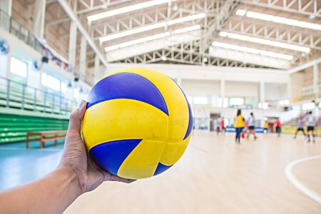 left hand: left hand holds a volleyball