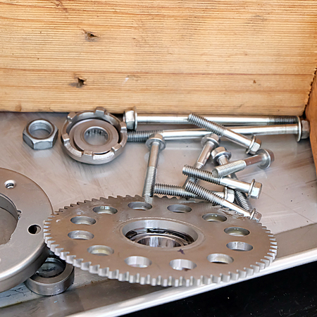 nuts and bolts: Steel gears, nuts, bolts, and wrenches. pieces of equipment in the system.