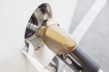 White car at gas station  Refueling hose. Petrol filling station