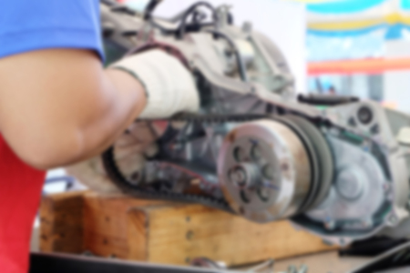 disassembly: Blur image hands of disassembly kit motorcycle in repair service.